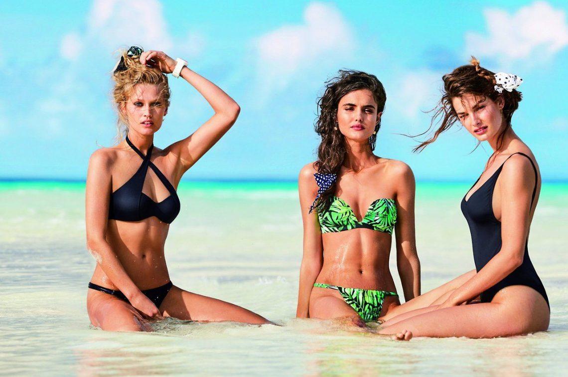 3 girls wear bathingsuits sitting in the sea