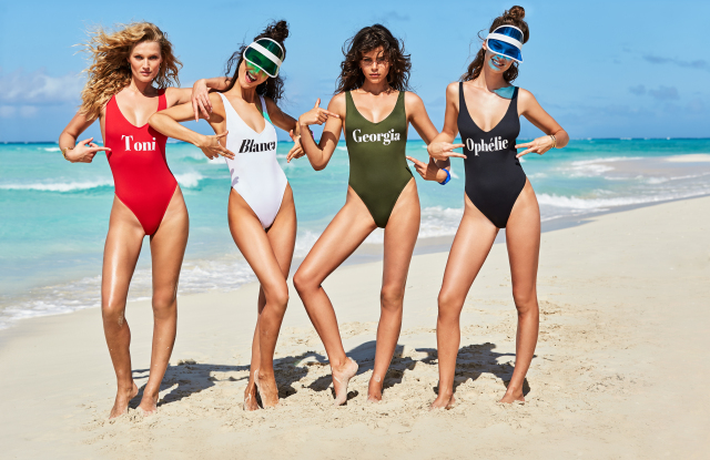 4 women in bathing suits posing in the beach
